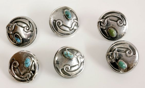 A cased set of sterling silver Arts and Crafts Cymric buttons, c.1900, by Liberty & Co. The set of six circular buttons, each one rub set with an oval cabochon turquoise, with relief whiplash decoration to a lightly hammered ground, Birmingham 1904, the case with silk-lined lid to read 'Liberty & Co. Ltd., Regent St., London'