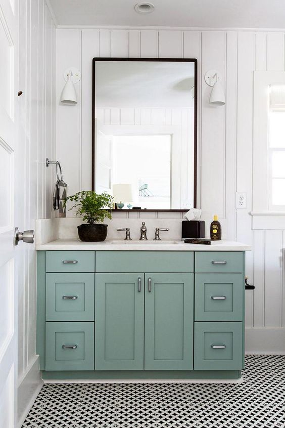 Love this minty almond green cabinet under the marble sink, with black framed mirror, white sconces, and black and white patterned floor tiles in this adorable country chic bathroom.: