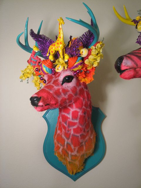 HowToConsign.com suggests: Turn a mounted deer head into a fantasy being (see the thrifted kids' toys and Happy Meal giveaways there in the head dress?)