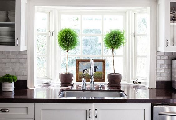 """Bits of color are added to the kitchen through easy-to-change accents such as greenery and a vintage painting. """"I like that it's clean, fresh, white, and bright,"""" says Allison."""