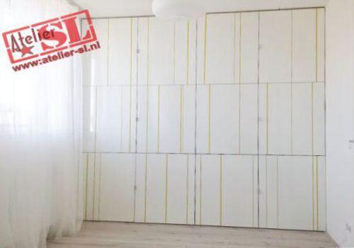 Inbouwkast met deuren van hoogglans HPL. Afmetingen: 266 x 265 x 40 cm. (BxHxD). Op maat gemaakt. Op de deuren zijn streepjes van verschillende breedten en vormen gefreesd, en naar kleurwens van de klant geschilderd. De kast heeft 12 deuren, en legplanken. Info: info@atelier-sl.nl en www:atelier-sl.nl