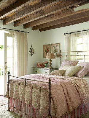 Farmhouse Room  A light-filled space is warmed with shades of dusty pink and pale green, while antique finds suggest a detail-rich story. Pink linens from Elizabeth Allen Atelier pair nicely with an antique quilt atop a tag-sale iron bed and soften aged, wooded beams ripe with sturdy character.