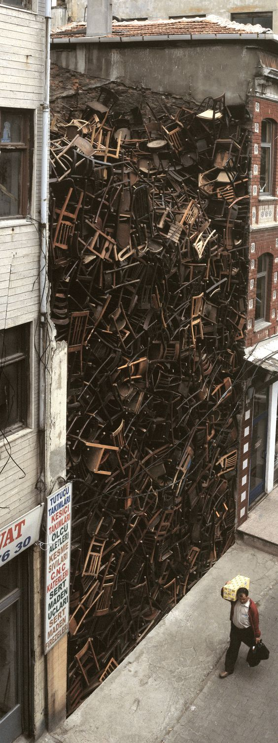 Doris Salcedo. 1,550 wooden chairs piled high between two buildings in central Istanbul.: