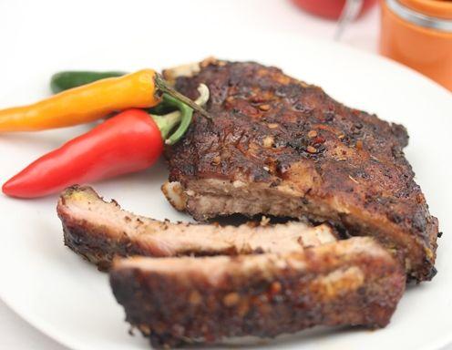 Für die scharfen Spareribs das Fleisch abspülen und trocken tupfen. Eine Marinade aus Chiliöl, Cayennepfeffer, Tabasco, Sojasauce und Zitronensaft