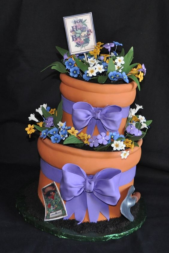 flowerpot cake with gumpaste flowers, shovel and bows. seed packets are print on frosting sheets