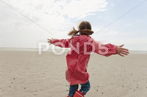 Germany North Sea St Peter Ording Girl 6 7 In Rain Coat Playing On Beach Stock Image 27189146