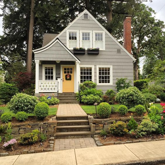 adorable grey cottage with white trim and yellow door