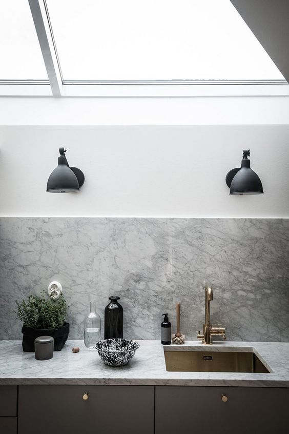 This Swedish apartment is the perfect example of 'hygge' with it's black and brass details, rust red roof and warm natural textures throughout the space.