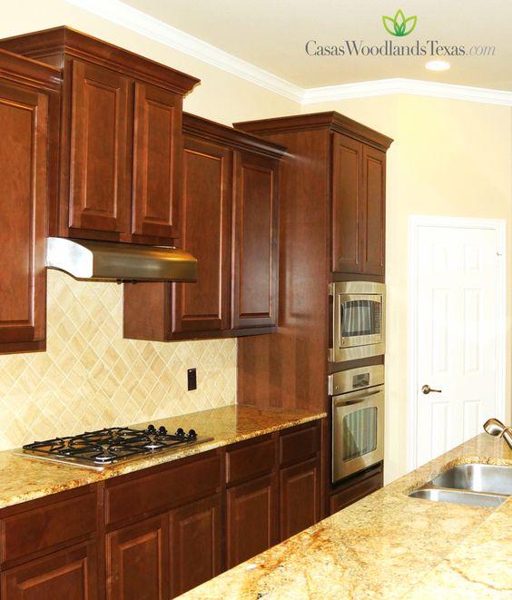 La cocina est equipada con gabinetes de madera for Gabinetes de cocina modernos