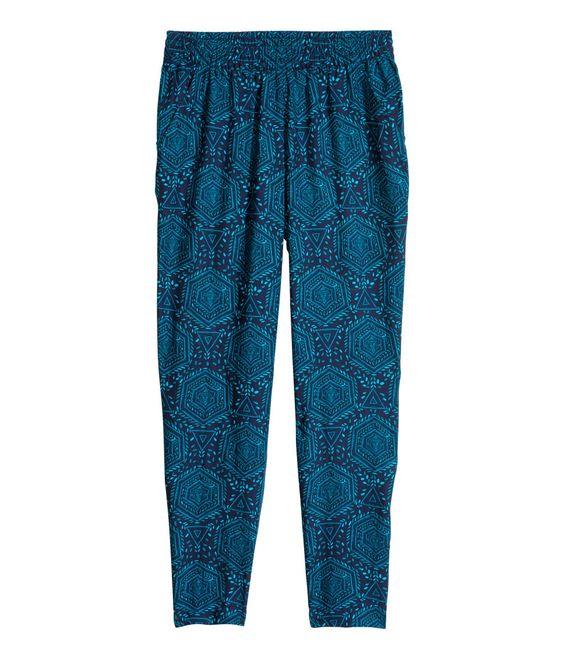 80 kr Petrol/Mønstret. Vide bukser i let, vævet kvalitet. De har elastik i taljen, ben, der bliver smallere forneden, og sidelommer.