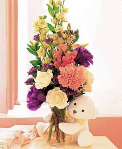 Fresh cut mix of spring flowers in a clear glass vase with a cuddly surprise peaking out from behind the vase!   #denverflorist #denverflowers #denverflowerdelivery