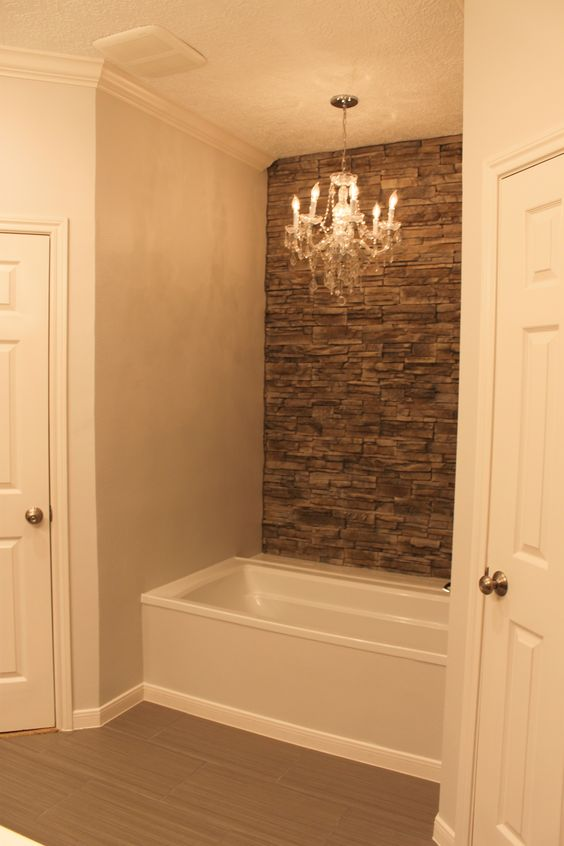 My tub with faux stone wall accent wall and chandelier.