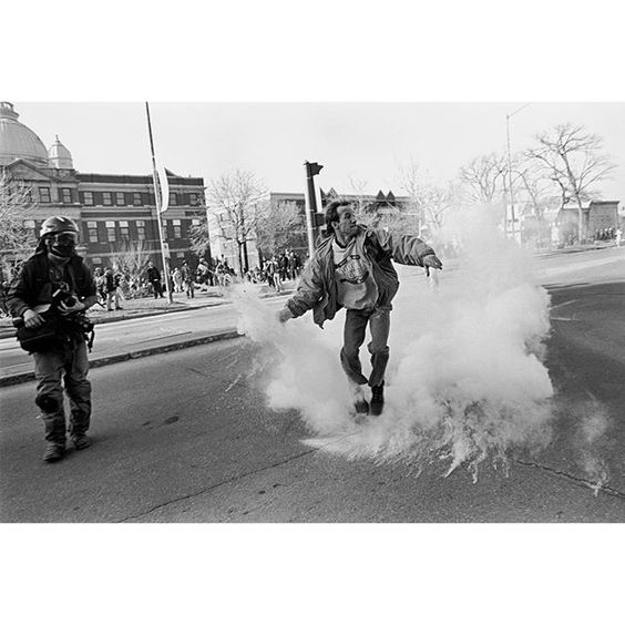 CANADA. Quebec. Quebec City. April 20-22 2001. A protester picks up and heaves a tear gas canister that was shot at the crowd of protesters by RCMP riot police after part of the wall was torn down. ( Larry Towell/#MagnumPhotos) @larrysgeneralstore by magnumphotos
