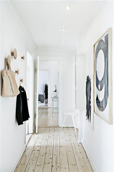 Schlichter Flur mit großen, runden Garderobenhaken. Platzsparend und minimalistisch.