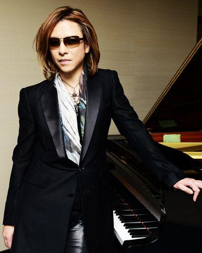 黒いジャケットを着てピアノに手をついているXJAPAN・YOSHIKIの画像