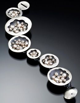 Enigma bracelet of oxidized and polished sterling, 14k, 18k, white sapphire and pearls by Carol Fugmann.