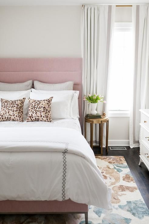 A Gold Bedside Table Is Placed Beneath A Window Dressed In Gray Border Curtains And Beside A In 2020 White Bedroom Decor Grey And White Bedding Velvet Upholstered Bed