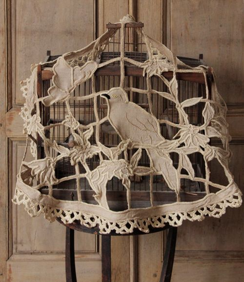 Antique embroidered bird cage over (not sure how it helps the bird sleep, but hey, it looks good!)