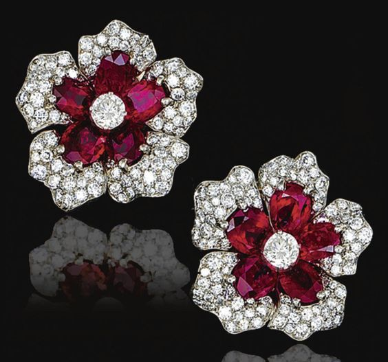 PAIR OF RUBY AND DIAMOND EAR CLIPS, VAN CLEEF & ARPELS, 1952. Each designed as a flower head, set with oval rubies and brilliant-cut diamonds, mounted in platinum, signed Van Cleef & Arpels and numbered, French assay and maker's marks, case.:
