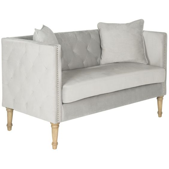 A loveseat to love at first sight, the Sarah tufted settee is a transitional update of classic chesterfield and tuxedo sofa styles. Covered in chic grey velvet, with button-tufted back and silver nailhead trim, it features two decorator throw pillows. Sophisticated yet cozy, the Sarah settee rests on beautifully turned Louis XVI legs in a washed oak finish.