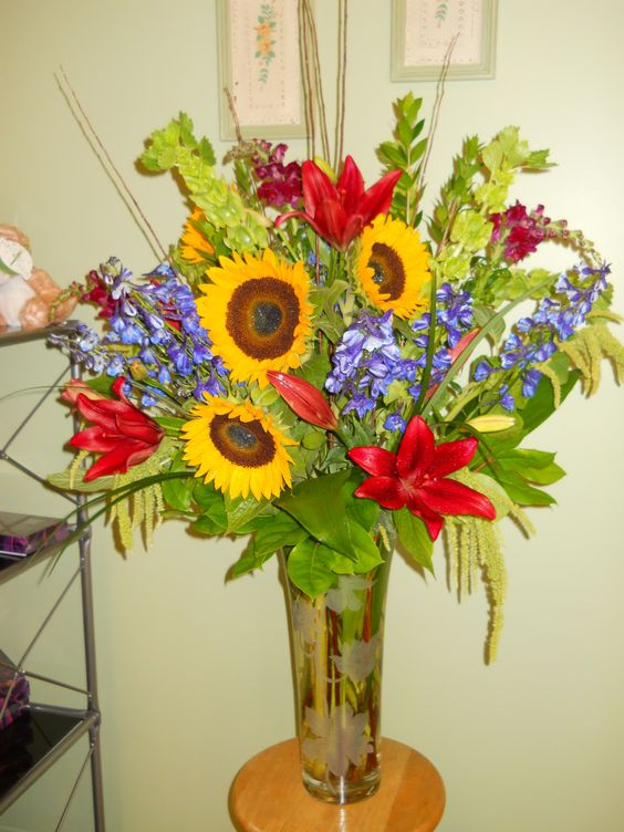 Saturated Summer Colors by Texas Blooms (sunflowers, rusty red lilies, blue delphinium, bells of ireland, burgundy snapdragons, green hanging amaranthus, mixed foliage)