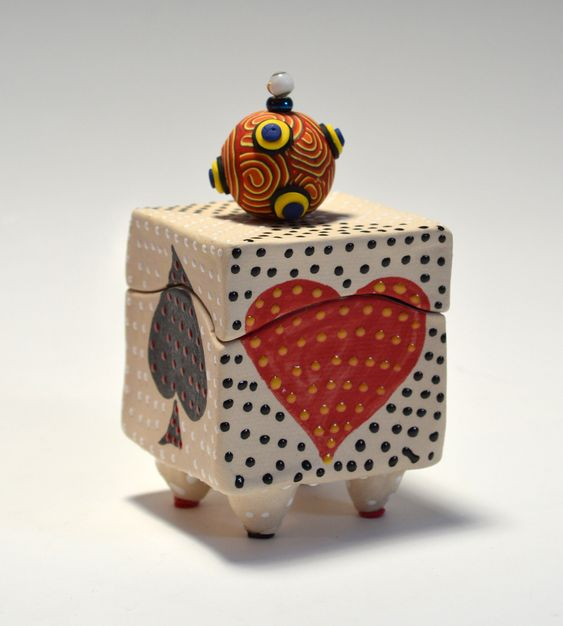 Playing Card Box by Vaughan Nelson. Slab built ceramic box. Decorated on each side with each of the suits from a playing card. Finished off with a polymer clay bead. Each piece is unique. Exact patterning will vary slightly from piece to piece.