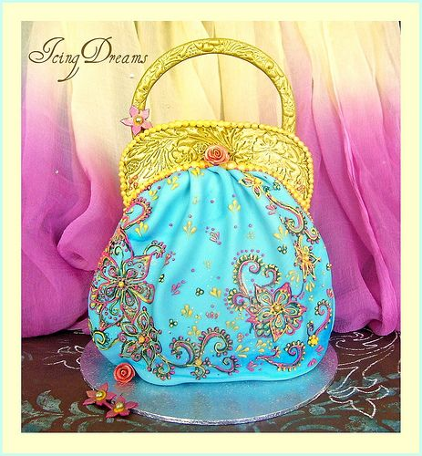 """Totally edible cake made from gumpaste, around 6"""" tall in aqua. The handle and clasp area are embossed and painted with gold lustre paint.  I drew (with edible pens) the black henna design on the bag then piped in bright pink and yellow highlighting  Fashion Plus! http://socialpagemagic.com/link/tmbagsale"""