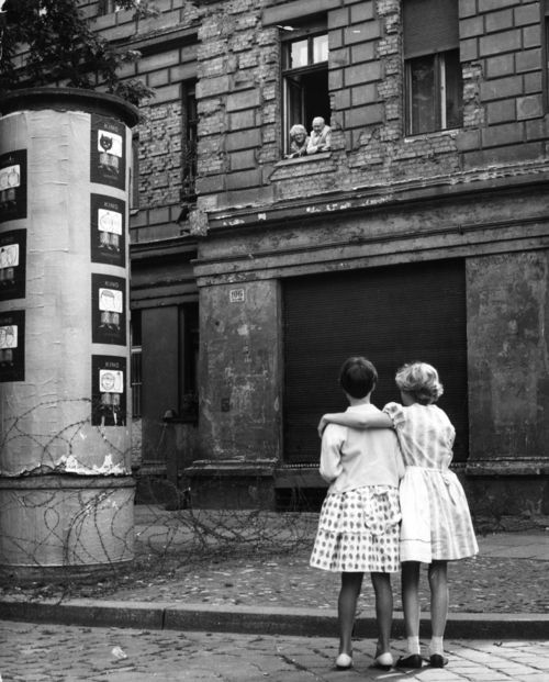Two young girls in                                                a West Germans street                                                chat with their                                                grandparents in the                                                window of their home in                                                the Eastern sector,                                                separated only by a                                                barbed wire barricade.                                                It was a common                                                occurrence for families,                                                who had once only lived                                                on the opposite side of                                                the street from one                                                another, to become                                                separated by the ever                                                growing Berlin Wall.: