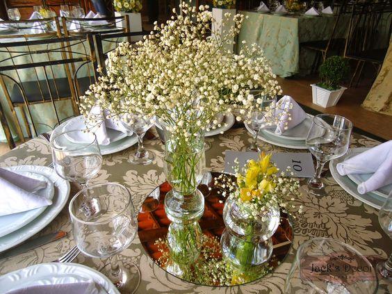 Arranjo da mesa dos convidados com gypsophilas (mosquitinhos) e alstromélia amarela em souplá de espelho