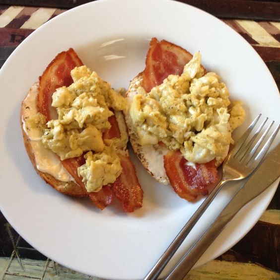 Lightly toasted onion bagel with cream cheese, smoked streaky bacon and scrambled eggs