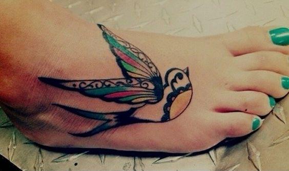 tatouage hirondelle multicolore sur le pied d'une fille