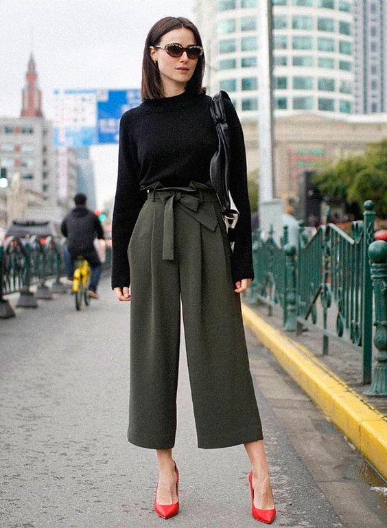 Lena Lademann usa calça clochard com tricot preto e scarpin vermelho.