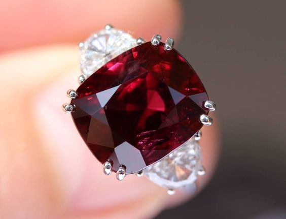 Pigeon blood ruby 13.30 Cts natural from Madagascar set in white gold with 2 half moon brilliant cut white diamond shoulders of 1.89 Cts - rare combination of clarity, size and color.