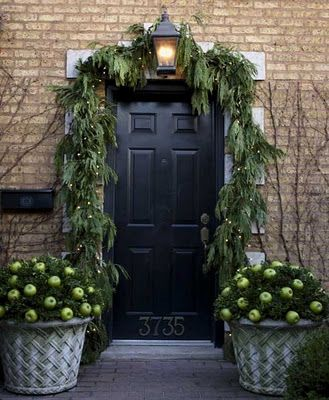 Christmas front door with long, drooping garland and apple topiaries