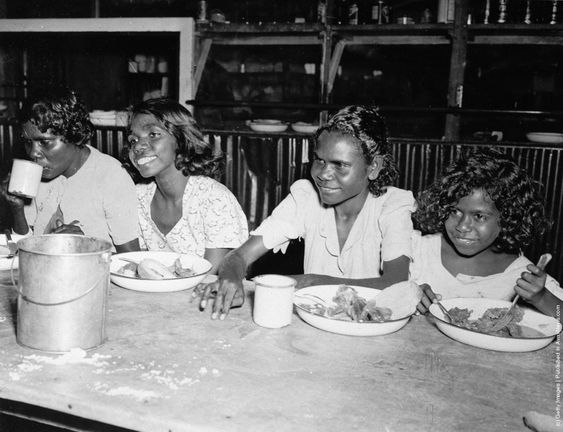 A group of Aborigine school girls eating at a communal table. (Photo by Three Lions/Getty Images). Circa 1955