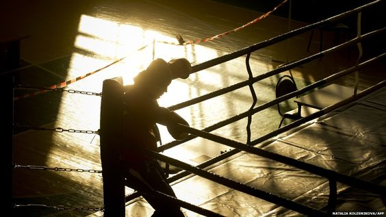 A junior female boxer takes a rest shortly after a sparring session