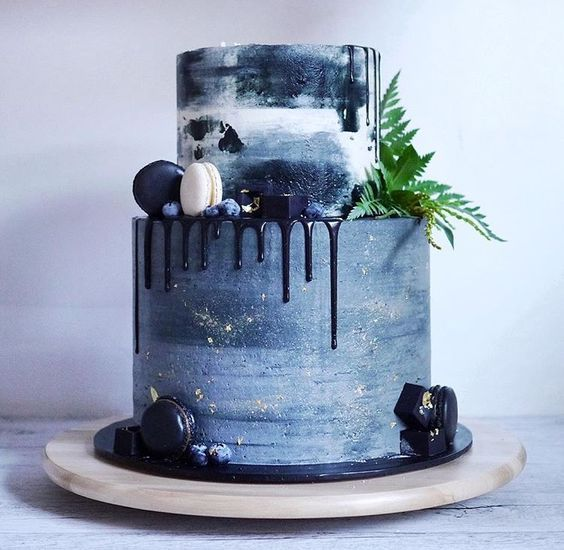 a slate grey wedding cake with navy drip, gold touches, greenery and navy and cream macarons for a modern wedding