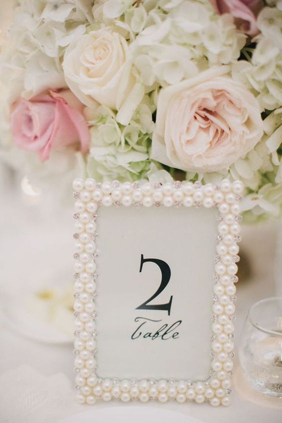 Pick out pearl picture frames (or make some yourself) to mark the wedding reception tables. | Image via Want That Wedding