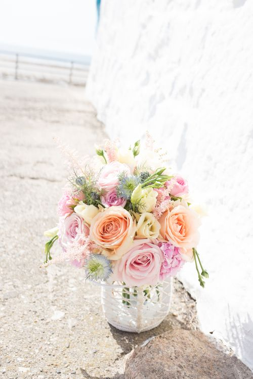 Pastel bouquet of peach and sweet avalanche roses, blue nigella, lemon yellow lisianthus, pink hydrangeas and spray roses. Wedding flowers by London based Floral designers Okishima & Simmonds. www.okishimasimmonds.com