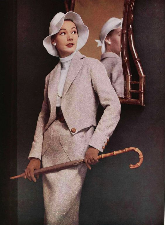 """sheisanniebelle:  Jacques Fath has chosen a greige tweed for this tailored dress, the belt of which is worn on or under the vest, the blouse has a rolled collar effect. The hat of light colored felt is called """"à la Garbo."""" Photo Pottier, 1952"""