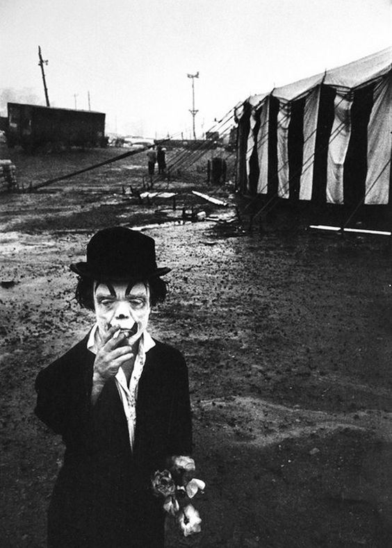 Clown smoking a cigarette outside a circus tent
