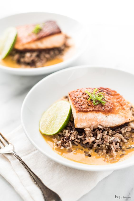 Pan seared salmon on a bed of wild rice in a rich and creamy ginger and coconut curry broth.: