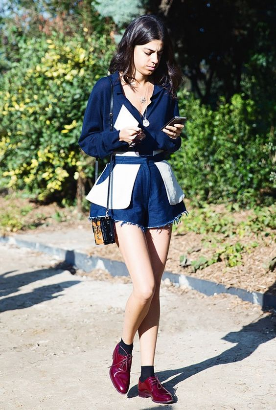 Leandra Medine wears a button-down blouse with raw hem denim shorts, black socks, burgundy oxfords, layered necklaces, and a mini Louis Vuitton bag