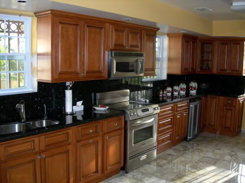 Golden oak kitchen cabinets with black countertops for Brown kitchen cabinets with black granite