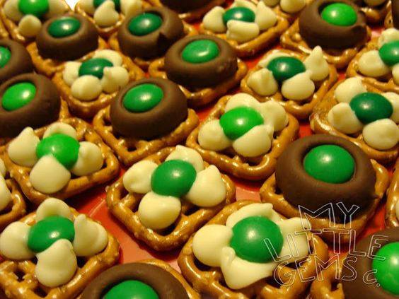 All you need is pretzels, Hershey's kisses, chocolate chips- white ones, and green M&M's.  Preheat your oven to 200 degrees.  Lay out your pretzels on the cookie sheet.  Place one Hershey's kiss or 4 chocolate chips on each pretzel. chocolate is soft- after about 5 minutes, take out of oven and place a green M&M in the middle. If you use the chocolate chips, you can use a toothpick to swirl it a little so it looks like a clover.