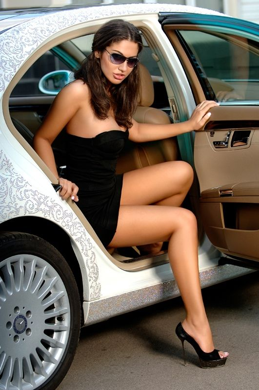 Wearing a short strapless cocktail dress with open toe platform heels she unfolds her lovely legs from the back of the car