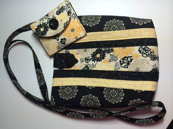 This crossbody bag and lining are made of cotton and measures 9 x 8.5 inches with a 52 inch strap. Has a button closure with fabric loop,and two inner pockets trimmed with contrast print as on the front of the bag. The wallet has three card pockets and a coin pocket with a Velcro closure. It is tri-fold with a Velcro closure and decorative button. Closed is 4.25 x 3.25 inches. Open is 4.25 x 8.5 in.
