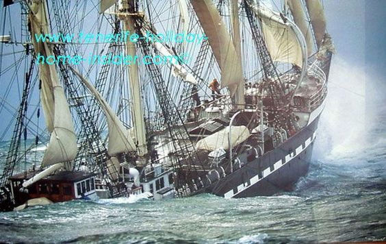 A large sailing ship is fighting ferocious seas. It's half submerged and doesn't look good.