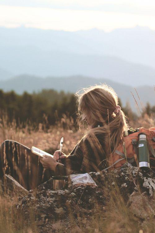 chica escribiendo en una libreta en el campo