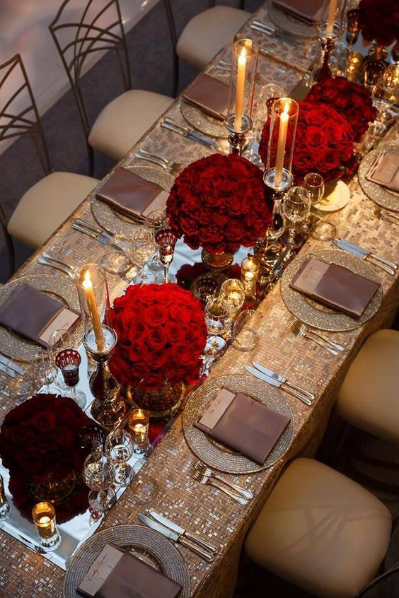 Long family table with mirrors and red compact arrangements.  use floating candles instead of tapers